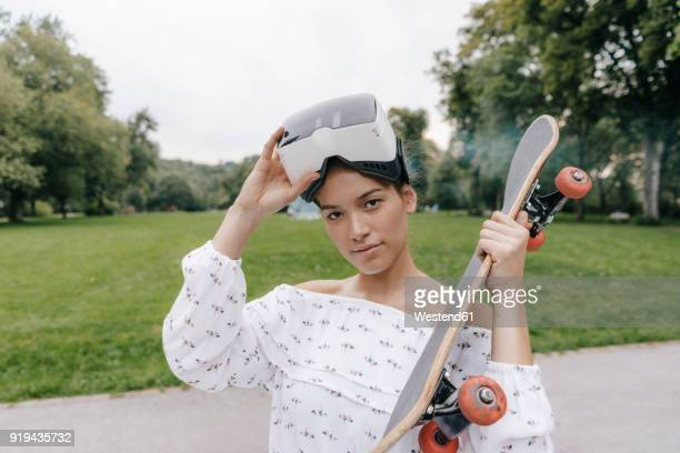 Portrait of young woman with VR glasses holding skateboard