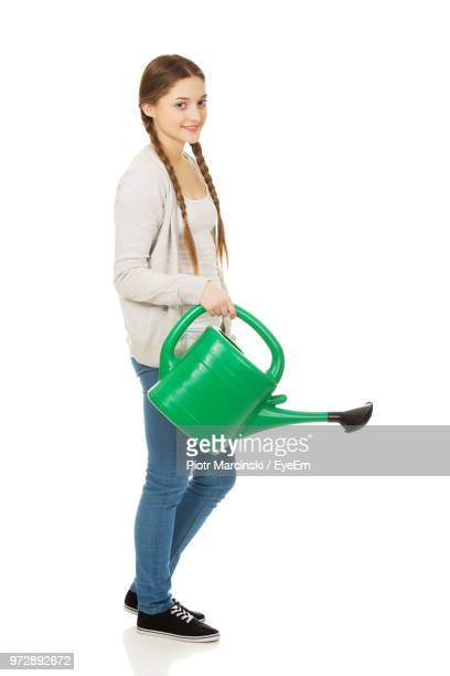 Portrait Of Young Woman With Watering Can Against White Background
