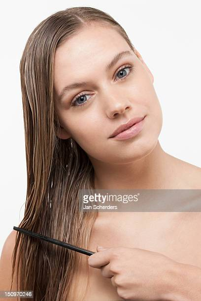 Portrait of young woman with wet hair and comb