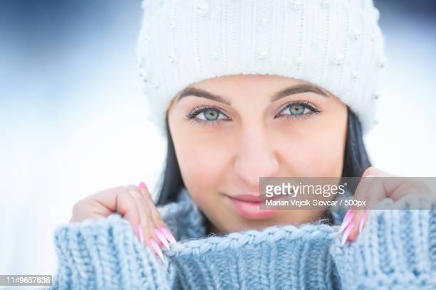 portrait of young woman with winter clothes sweater and cap - februar stock-fotos und bilder