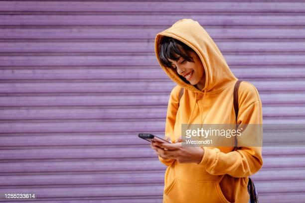 portrait of young woman with yellow hoodie checking smartphone in front of purple background - draagbaarheid stockfoto's en -beelden