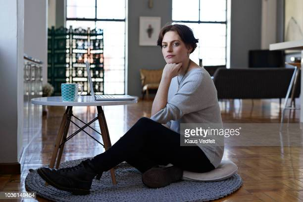 portrait of young woman working from home on laptop - gray jeans stock pictures, royalty-free photos & images