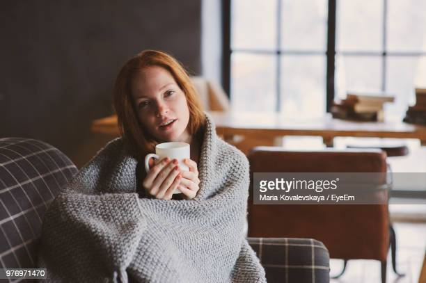 portrait of young woman wrapped in blanket holding coffee cup on sofa at home - deken stockfoto's en -beelden