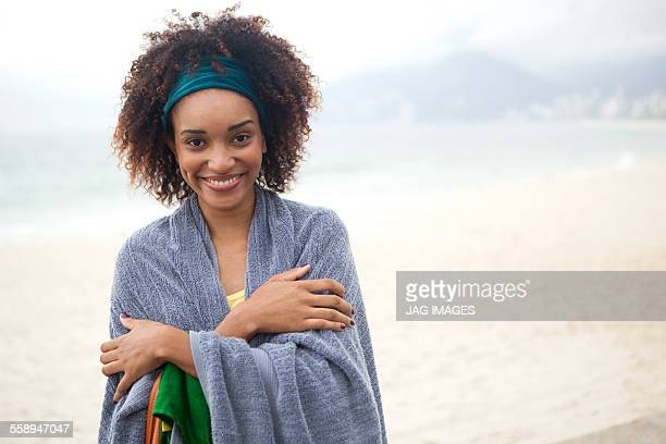 Portrait of young woman wrapped in blanket on Ipanema beach, Rio De Janeiro, Brazil