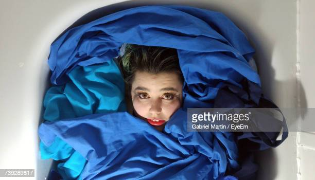 Portrait Of Young Woman Wrapped In Blue Fabric Lying In Bathtub