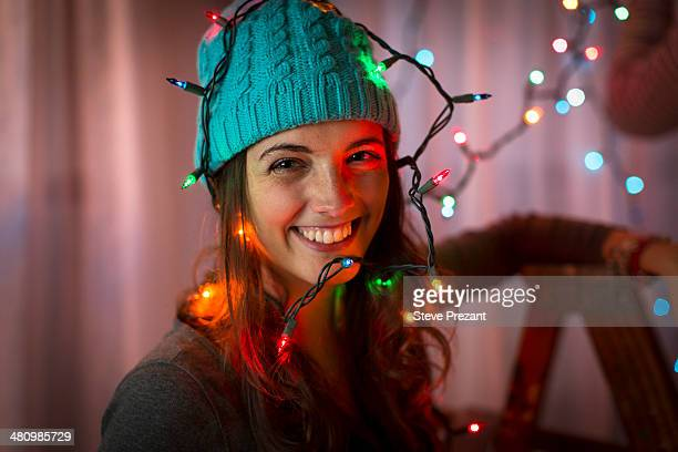 Portrait of young woman wrapped in christmas lights