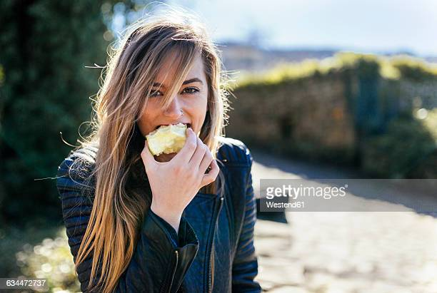 portrait of young women eating apple outside - apple fruit stock photos and pictures