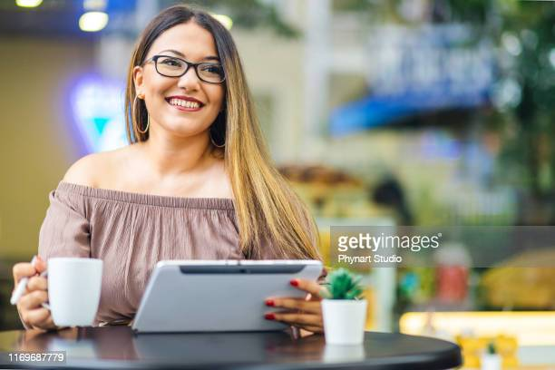 portrait of young women in cafe with coffee cup and tablet - illustrator stock photos and pictures