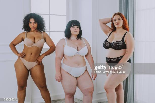 portrait of young women wearing lingerie standing against wall at home - bras stock pictures, royalty-free photos & images