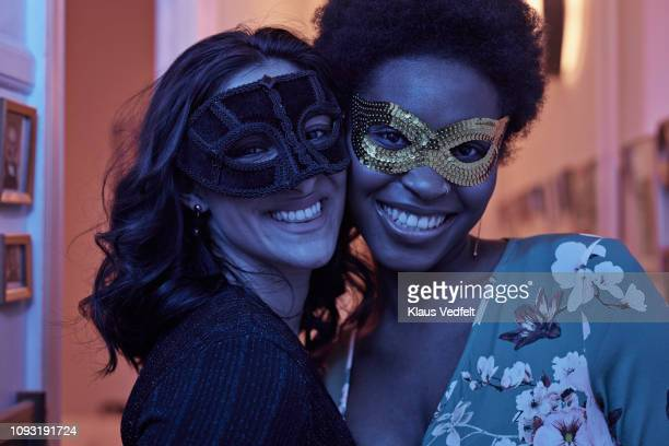 portrait of young women wearing masks at new years party - 25 29 years stock pictures, royalty-free photos & images