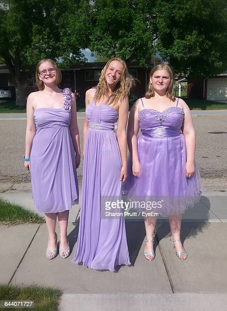 Portrait Of Young Women Wearing Purple Dress And Standing On Street
