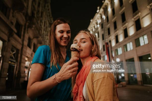 Portrait Of Young Women With Ice Cream Cone In City