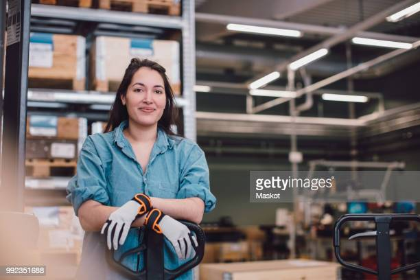portrait of young worker leaning on pallet jack at warehouse - beroep stockfoto's en -beelden