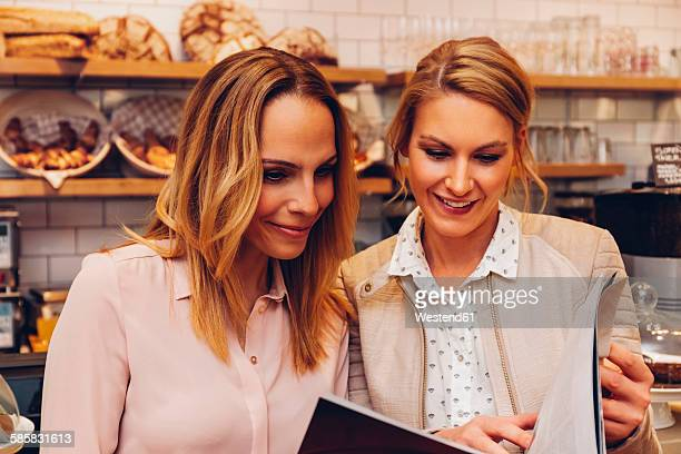 Portrait oft wo young women at a coffee shop reading menu card