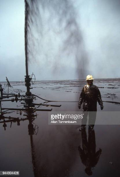 Portrait on an oil worker as he stands in pool from a well blowout during the Operation Desert Storm Kuwait 1991