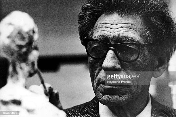 Portrait on July 18 1965 of the sculptor Alberto GIACOMETTI finishing up one of his works one of his lanky figures for an exhibition at the Tate...