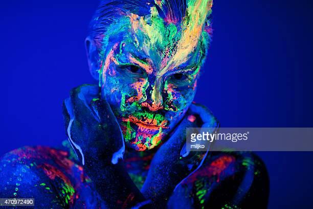Retrato pintados con maquillaje fluorescente bajo la luz ultravioleta.
