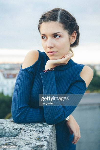 portrait: pensive young woman with with hair bun, looking away