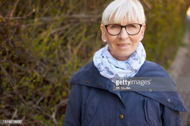 portrait photos of a 60-year-old woman with glasses and blond hair photographed outdoors in germany - 60 64 years stock pictures, royalty-free photos & images