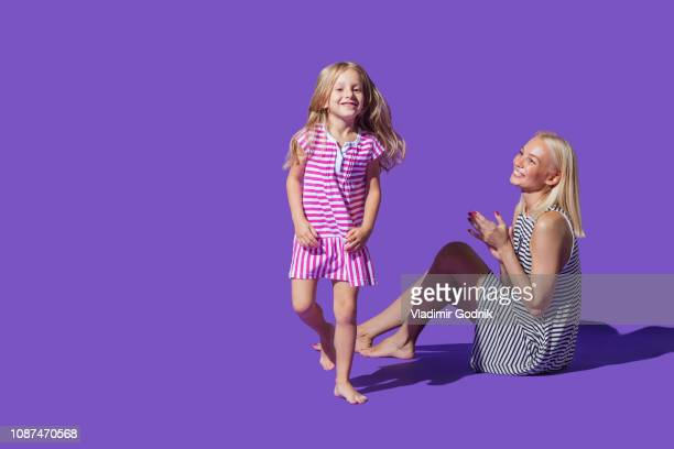 portrait playful mother and daughter in striped dresses against purple background - purple background stock photos and pictures