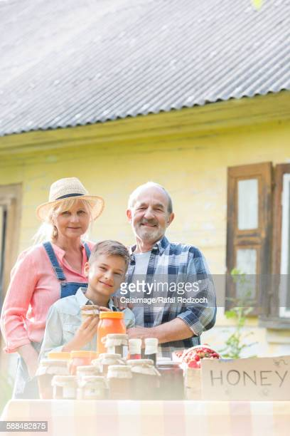 Portrait proud grandparents and grandson selling honey at farmerÕs market stall