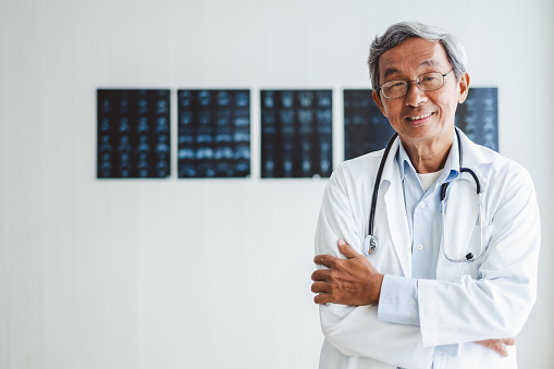Portrait senior asian doctor over radiography background, asian medical concept 1019862020
