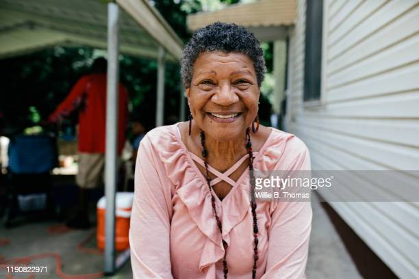 portrait senior black woman at family cookout - incidental people stock pictures, royalty-free photos & images