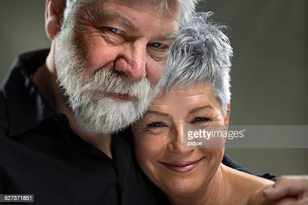 Porträt Senior paar umarmen einander, Blick in die Kamera.