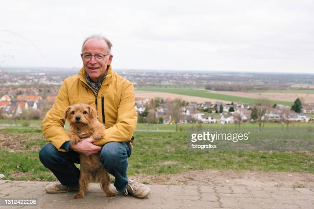 verticale : homme aîné avec son crabot, fond rural - norfolk terrier photos et images de collection