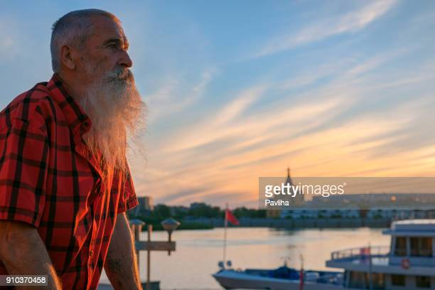 portrait senior man with white beard on a journey through the russian rivers,sunset - volga stock pictures, royalty-free photos & images