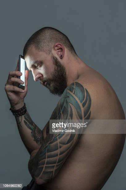 portrait serious bare chested man with tattoos holding smart phone - chest barechested bare chested fotografías e imágenes de stock