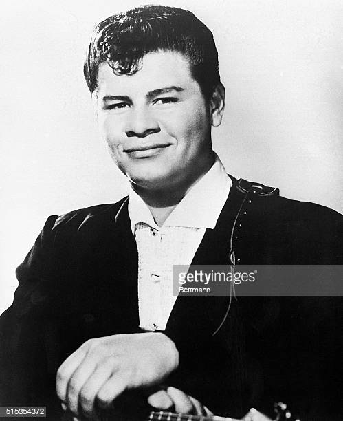 Portrait shows Ritchie Valens with his hands resting on his guitar. Undated head-and-shoulders publicity photo.