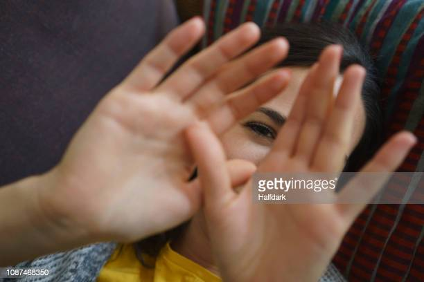 Portrait shy woman with hands in front of face
