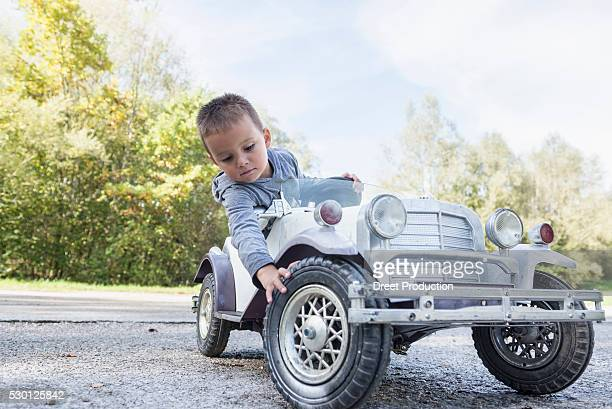 portrait small boy checking tire model vintage car - spaß stock pictures, royalty-free photos & images