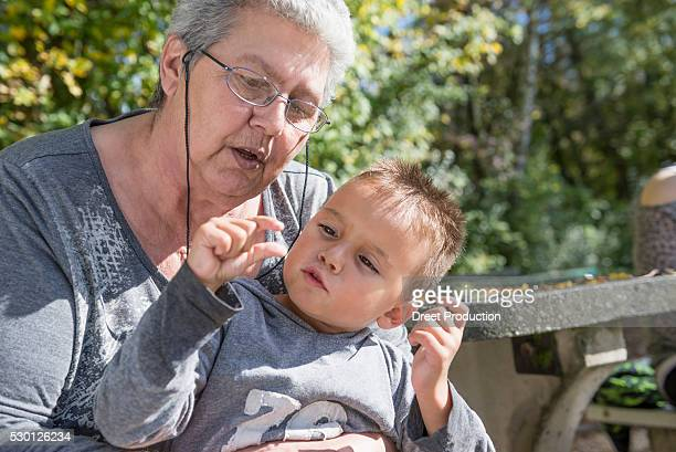 portrait small boy sitting on grandmothers knee - spaß stock pictures, royalty-free photos & images