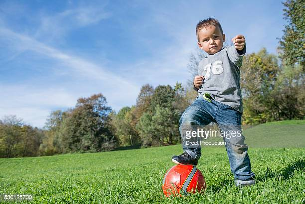 portrait small boy stepping on red football meadow - spaß stock pictures, royalty-free photos & images