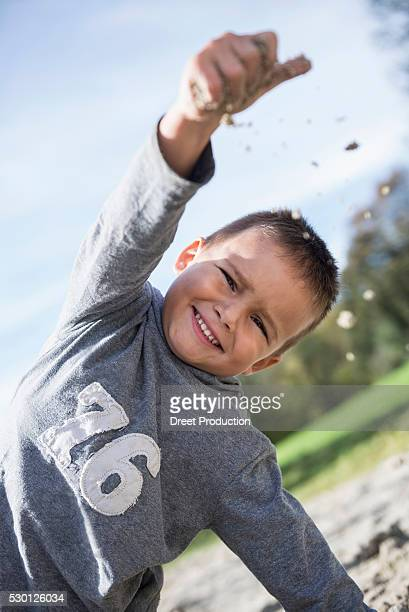 Portrait small boy throwing sand playground