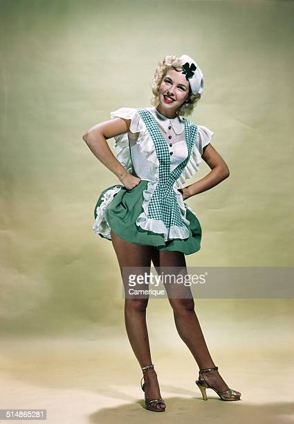 Portrait smiling blond woman pinup wearing green checked waitress uniform and hat with shamrock Los Angeles California 1949