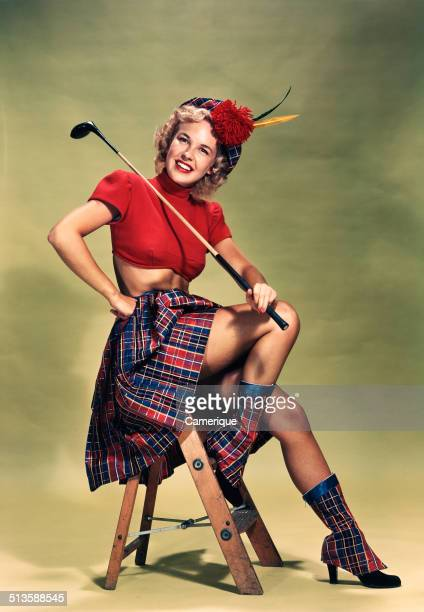 Portrait smiling blond woman pinup wearing plaid tam red cropped sweater plaid skirt and boots holding golf club Los Angeles California 1949