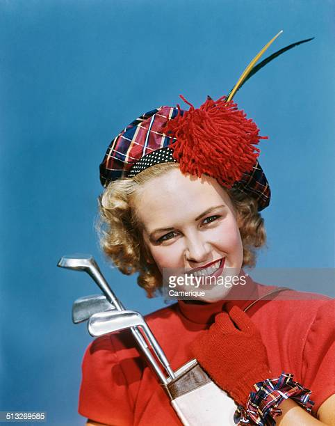 Portrait smiling blond woman wearing plaid tam red gloves holding golf clubs Los Angeles California 1949