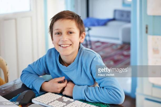 portrait smiling boy using computer at table - 8 9 jahre stock-fotos und bilder