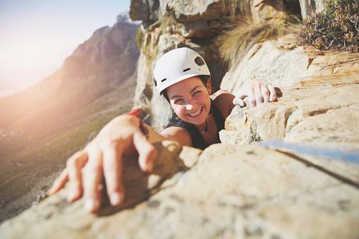 Portrait smiling, confident rock climber reaching for rock - gettyimageskorea