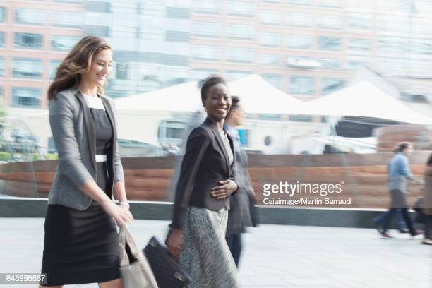 Portrait smiling corporate businesswoman walking outdoors