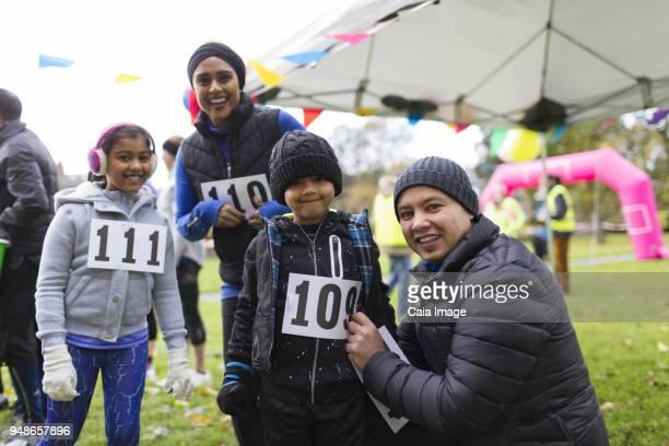 portrait smiling family preparing for charity run in park - 40s pin up girls stockfoto's en -beelden