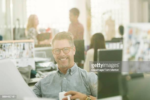 Portrait smiling fashion designer drinking coffee in office