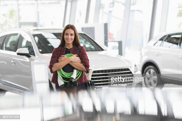 Portrait smiling female customer holding hybrid charging cable in car dealership showroom