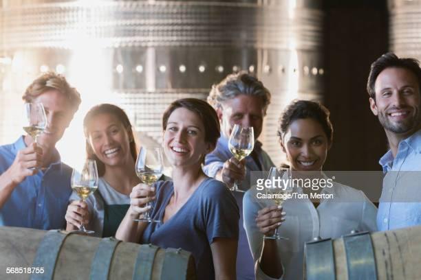 Portrait smiling friends wine tasting in winery cellar