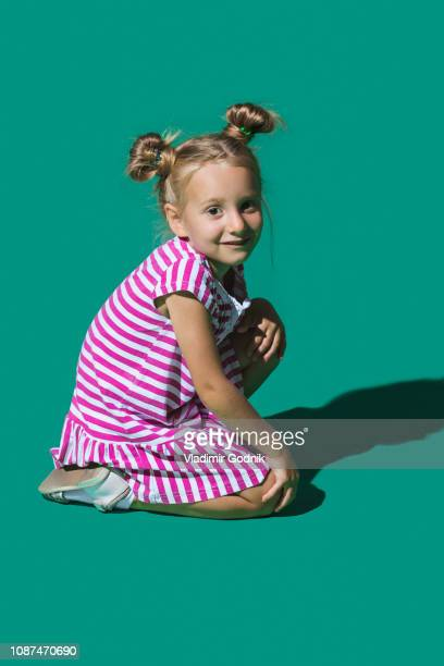 portrait smiling girl against green background - kneeling stock pictures, royalty-free photos & images