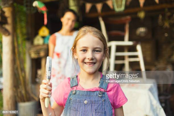 Portrait smiling girl holding paintbrush