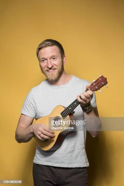 portrait smiling man playing ukulele - ukulele stock pictures, royalty-free photos & images